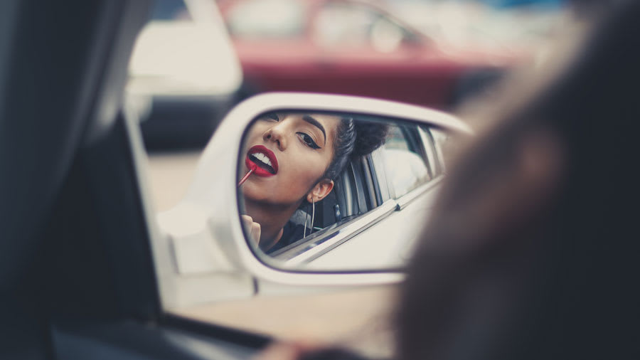 Busy woman applying makeup in care side mirror