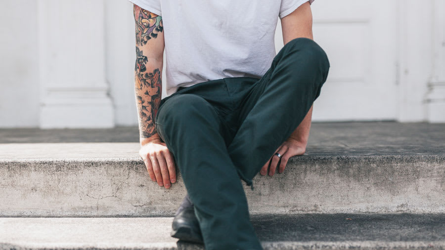 Man sitting cross-legged on steps with jeans, white tee shirt, and tattoos on right arm