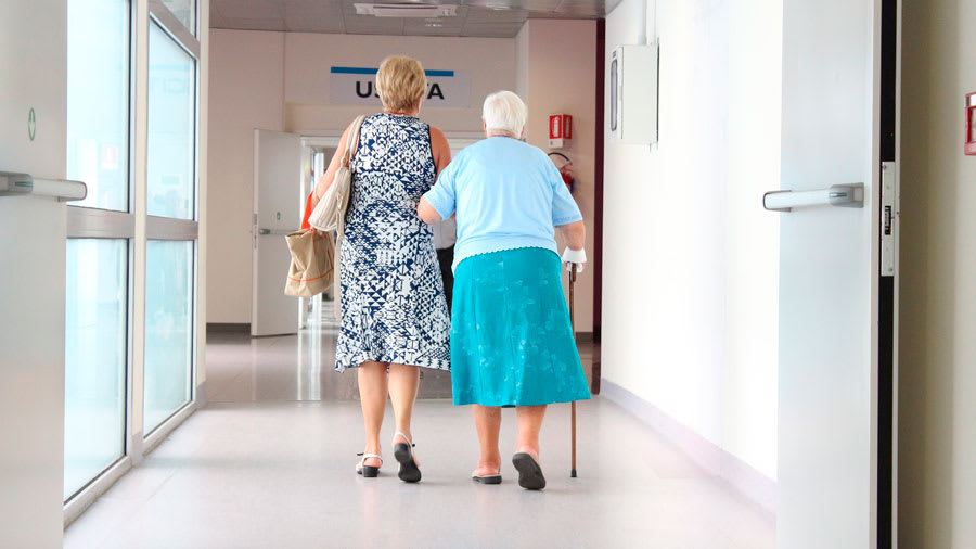 Elderly woman with swollen legs walking with cane in hospital and holding arm of another woman