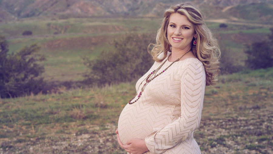 Pregnant woman with radiant face standing outdoors with mountains in background
