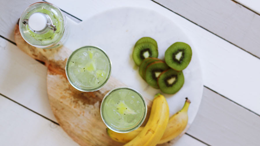 Lemonade, kiwi, and bananas on a wooden table