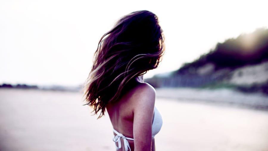 Beautiful brunette woman in white bikini on beach turned away from camera with beautiful skin