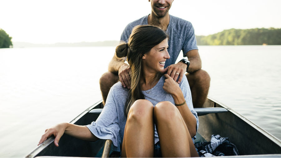 Brunette with clear face sitting on a canoe on the water with a man sitting behind her holding her shoulders