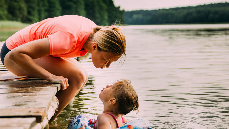 mother and daughter swimming in lake and sharing a kiss together