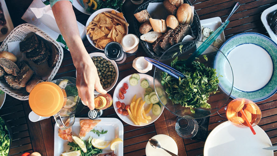 Hand reaching across dinner table crowded with many different foods
