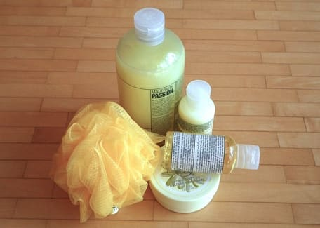 yellow bath set of personal care products shampoo conditioner body soap loofah