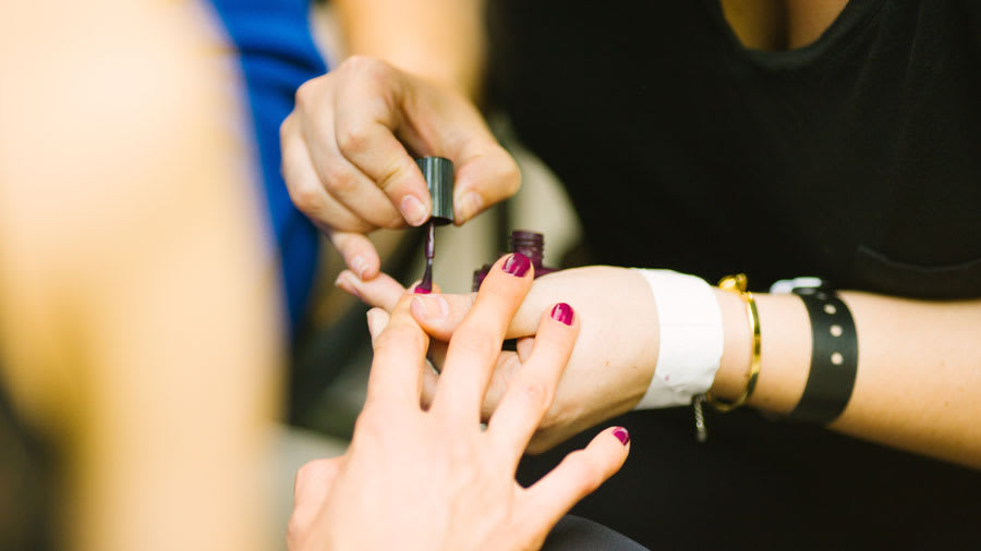 Red nail polish being applied to a woman's right hand index finger during a manicure