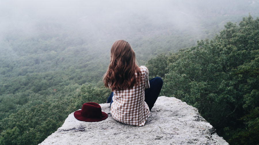Girl with long wavy brown hair wearing jeans and red plaid shirt and hat sitting on rock overlooking cloudy forest