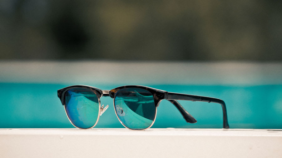 Polarized sunglasses with gold rims with pool in the background