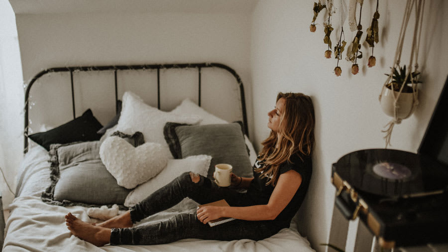 Sad woman sitting on bed alone with coffee in hand