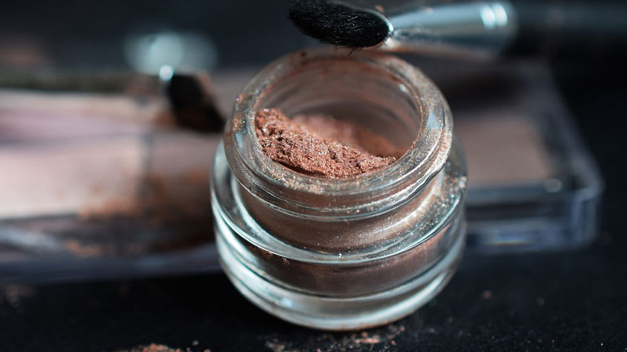 Sparkling brown makeup powder with brush and powder spilled on table