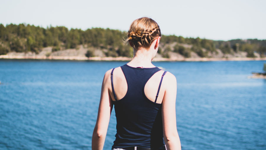 woman with braided hair in front of lake in tank top without acne