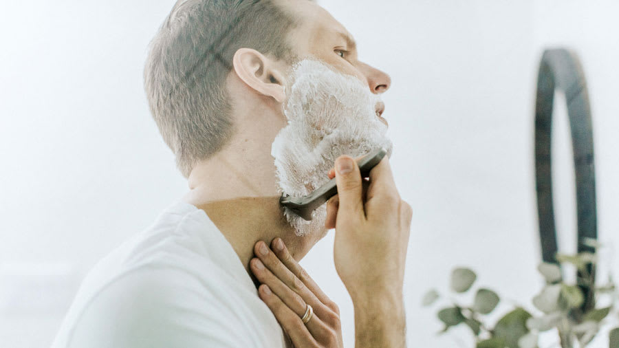 man shaving beard in front of mirror