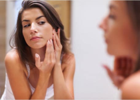Woman in white tank top looking at her face reflection in a mirror