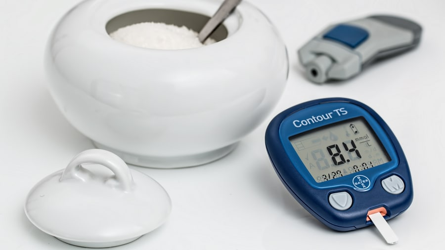 Sugar in white container with spoon next to stopwatch