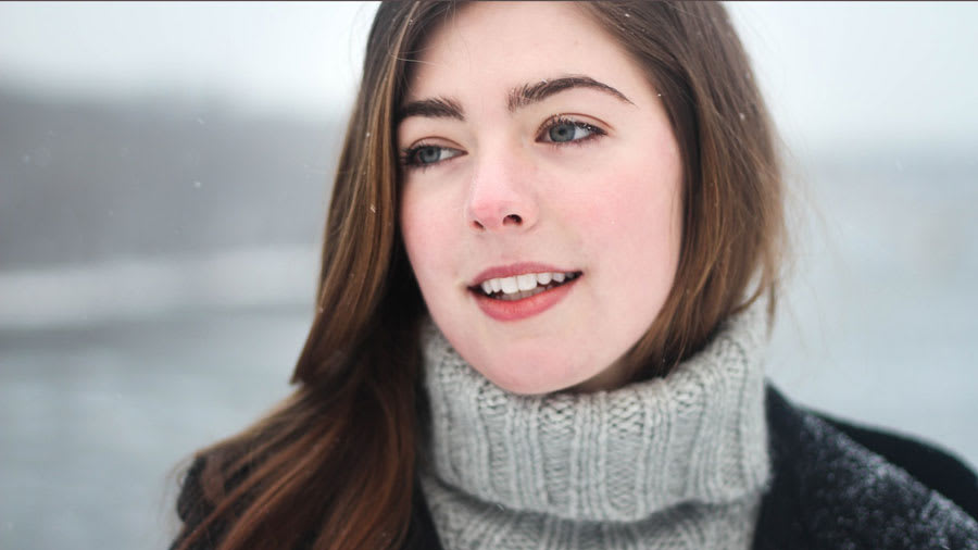 Brunette woman wearing grey knit sweater and black coat in winter