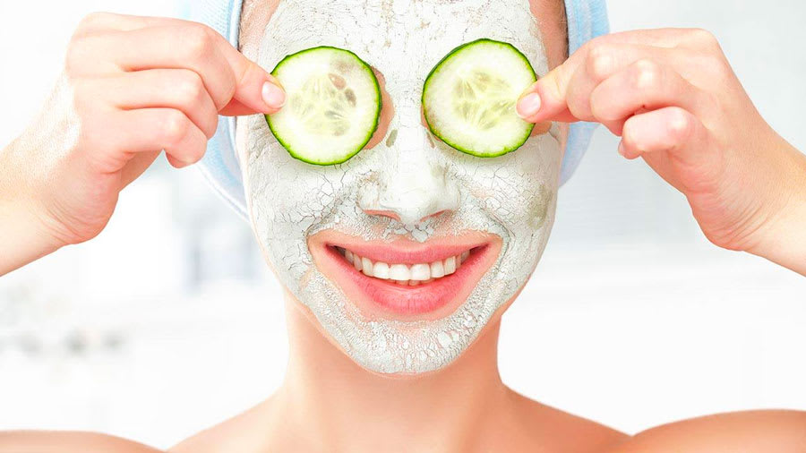Woman with face mask and cucumbers