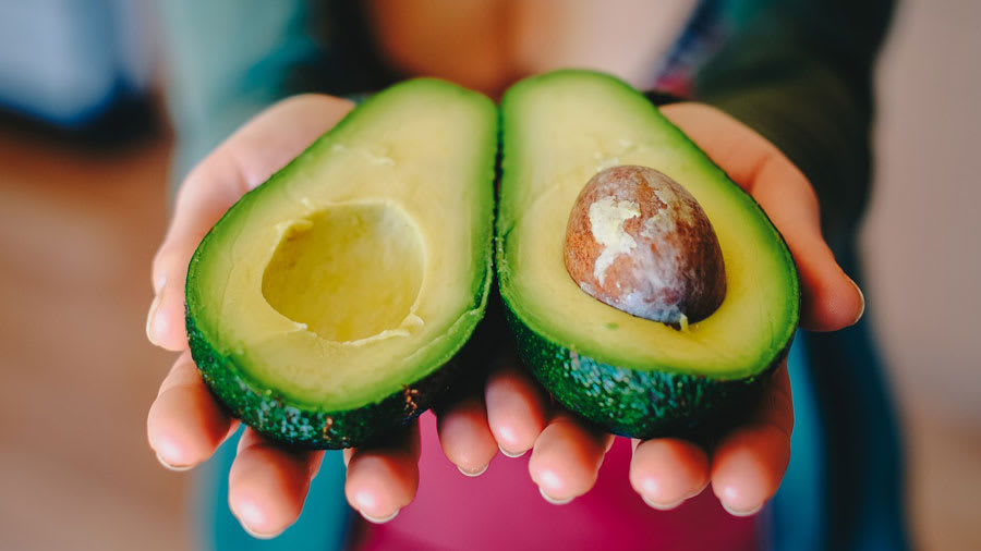 Two halves of an avocado being held in hands