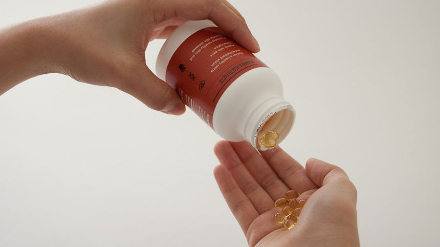 Multivitamins pouring out of bottle into hand