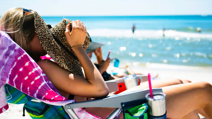Woman sitting in beach chair with hat over face with ocean in background