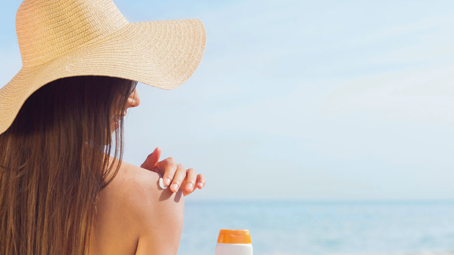 Brunette putting sunscreen on her shoulder on beach with straw hat