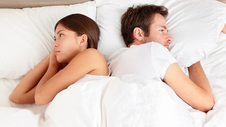 couple having issues during intercourse facing away from each other in bed