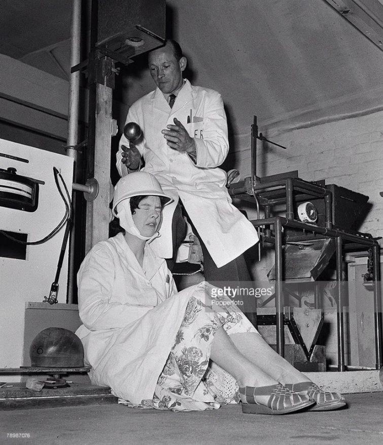 """Научные работники исследовательского центра """"Eliis Research laboratory"""" тестируют мотоциклетный шлем путём бросания на него стального шара, 1957 год. история, смотреть, фото"""