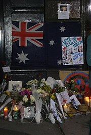 """Dark doorway and doorstep with section of footpath. On the lower part of the dark door is a partly obscured Australian flag with dark blue background; red and white crosses on top left, large white star underneath and three white stars at the right with others obscured. Obscuring the right side of the flag is a white sheet with light blue writing, """"Love + Miss You Always Heath"""" with two red hearts nearby, other writing includes """"I'll never quit you"""" in darker blue, more writing is indistinct. This sheet also has six photos of a man. Above the flag, on the door is a smaller sheet with a photo of a man and indistinct writing below. On the doorstep and section of footpath are some 14 groups of flowers wrapped in plastic or paper, together with nine or so cards, five or six lit candles, and more photos. On the right side is a straw hat."""