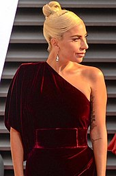 A picture of Lady Gaga in a burgundy one shoulder dress, looking to the right.