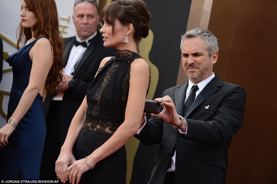 Snap happy: Oscar nominee Alfonso Cuaron took a snap of the back of girlfriend Sheherazade Goldsmith's dress