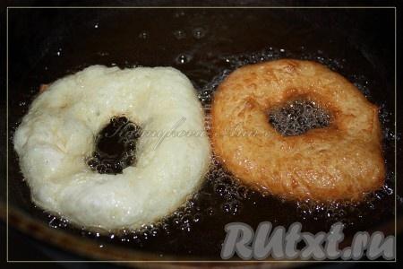 Нагреть хорошо масло в казане (или удобной для вас посуде), брать по одной заготовке пальцами, по середине проделывать дырку в пышке, растягивать ее в диаметре примерно до 6-7 см и отправлять в горячее масло (если помещается 2-3 пышки, то делайте столько, я по 2 жарила, процесс достаточно быстрый). Готовые пышки откинуть на бумажное полотенце.