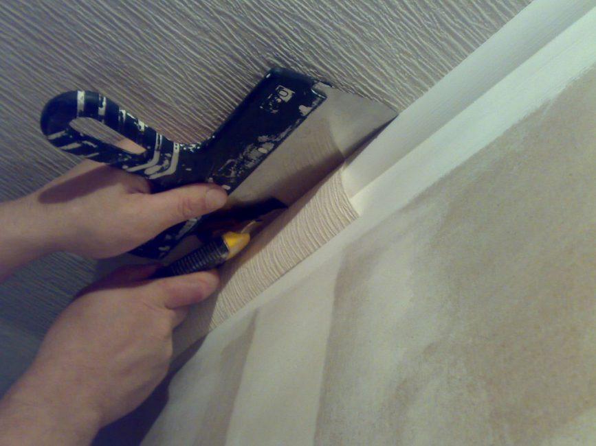Заделы полотна у потолка и пола отрезают по лезвию шпателя