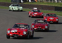 Five racing cars in line, taking a right-hand corner on a race track
