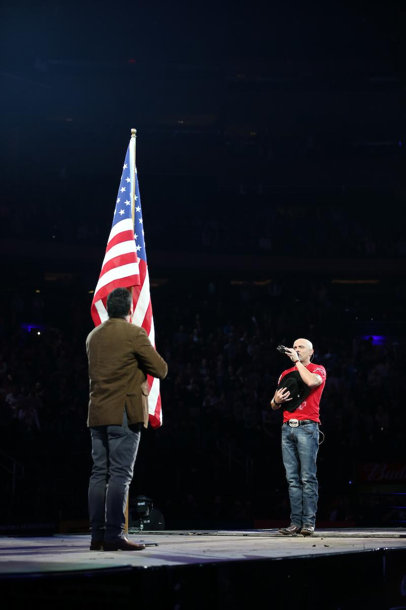 Rich Miller presents the American Flag and Ryan Weaver sings the National Anthem in the opening of the second round of the 25th PBR: Unleash The Beast Monster Energy Buck Off at The Garden in New York City. Photo by Andy Watson