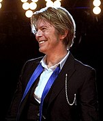 A man smiling; he has brown hair and wears a suit jacket and vest, and a white shirt open at the collar. His blue tie is not fastened.