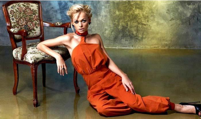 Анна Хилькевич сидит на полу в оранжевом комбинезоне