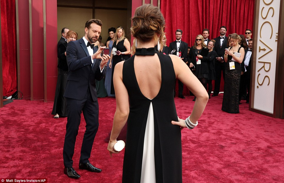 Snap happy: Jason Sudeikis took a picture of his fiance Olivia Wilde on the carpet