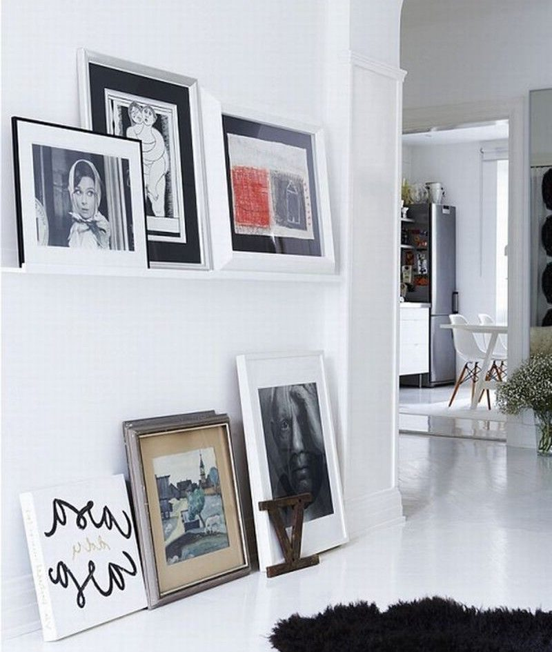 Фотографии в рамках на полу жилой комнаты