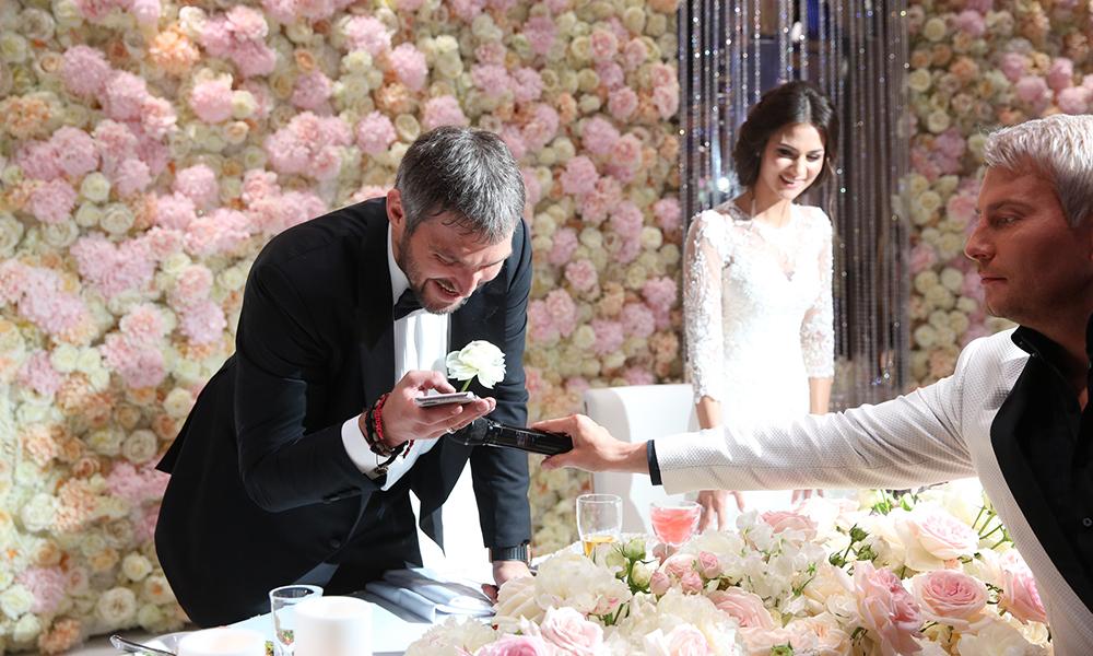 """В середине вечера, когда праздник был в разгаре, неожиданно выключилась музыка и ведущий Николай Басков с телефоном в руках подбежал к столу новобрачных. """"Саша, Настя, вам сам президент звонит, поздравить лично хочет"""", - предупредил Николай. Чтобы все гости могли услышать речь Владимира Путина, Александр включил динамик, а Николай поднес к телефону микрофон"""