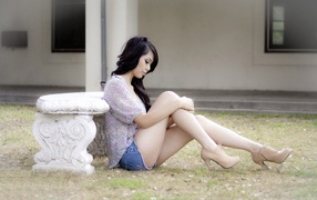Брюнетка сидит на земле у каменной скамьи