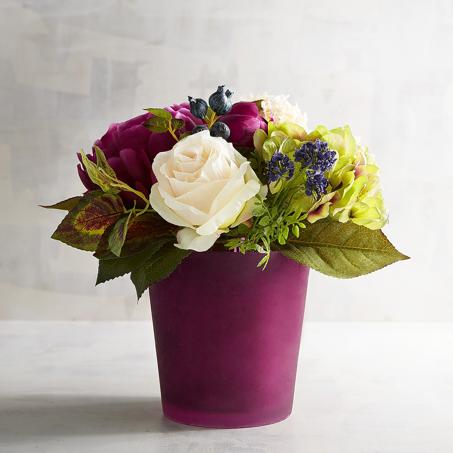 Faux Floral Arrangement in Magenta Glass Container