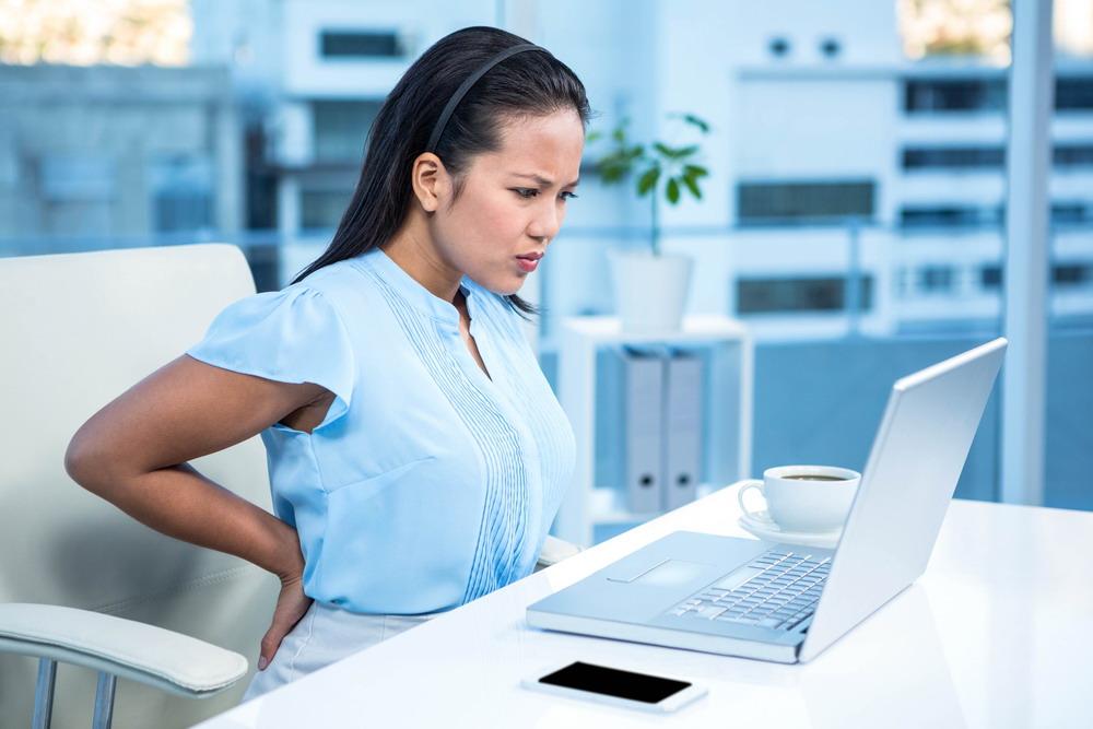 Sad businesswoman having back pain at her desk