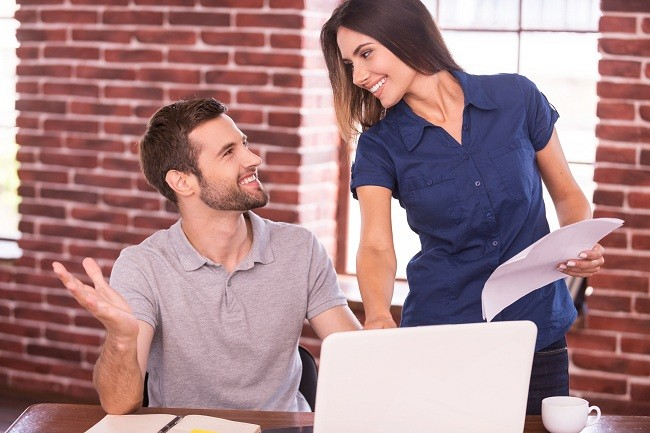 Creative collaboration. Cheerful young man sitting at his working place and gesturing while beautiful woman standing close to him and smiling
