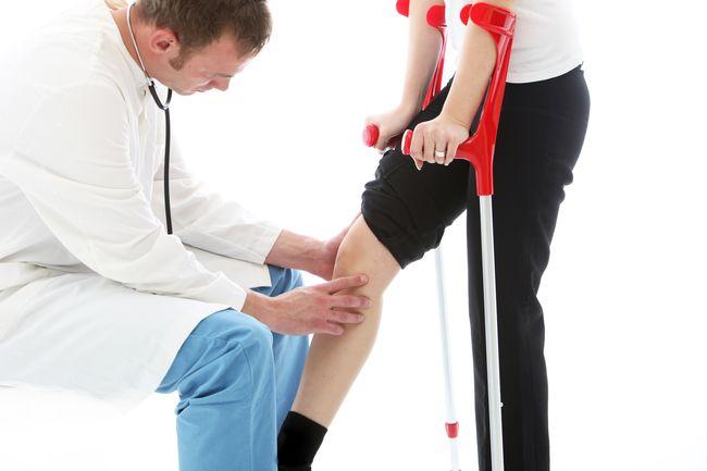 Orthopaedic surgeon examining woman's knee