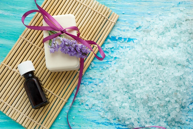 natural organic soap bottles essential oil and sea salt on a blue wooden table, Spa with flowers