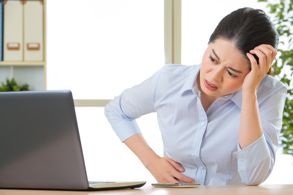 Young asian business woman with stomachache in office