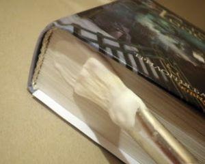 Промазывание клеем нижнего обреза книжного блока