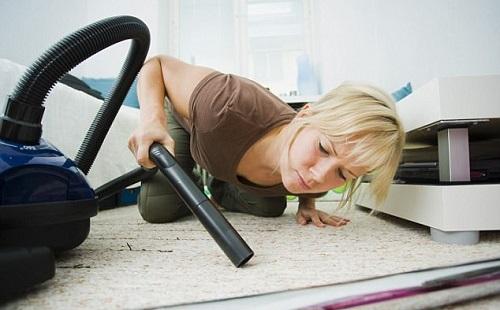 женщина очень тщательно чистит белый ковер трубой пылесоса без насадки