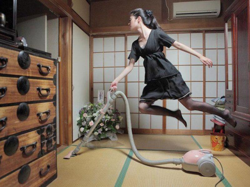 Парящая в воздухе девушка пылесосит в комнате по системе флай леди