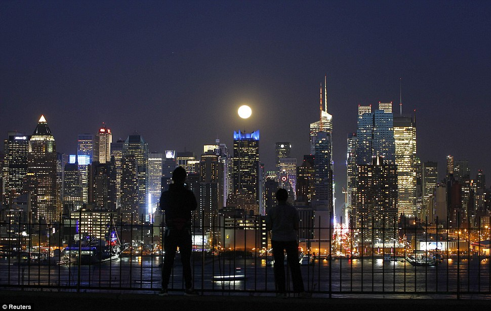 Moonlighting: People watch the full moon as it rises over the skyline of New York City near 42nd Street as seen across the Hudson River in Weehawken